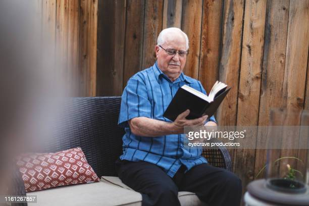 Mature retired adult male and Mature Retired Adult Female enjoying a life of leisure living enjoying reading outside in privacy-fenced patio on patio furniture
