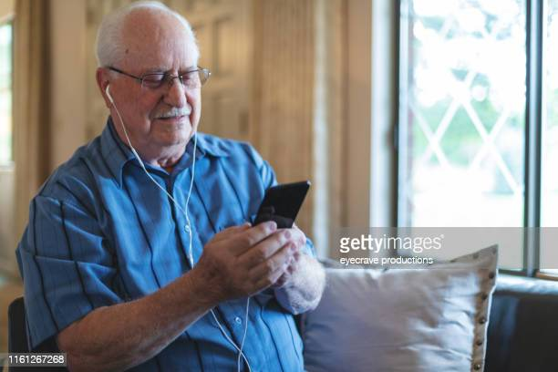 Mature retired adult male enjoying a life of leisure living inside on living room sofa listening to music and surfing the web on Smart phone technology