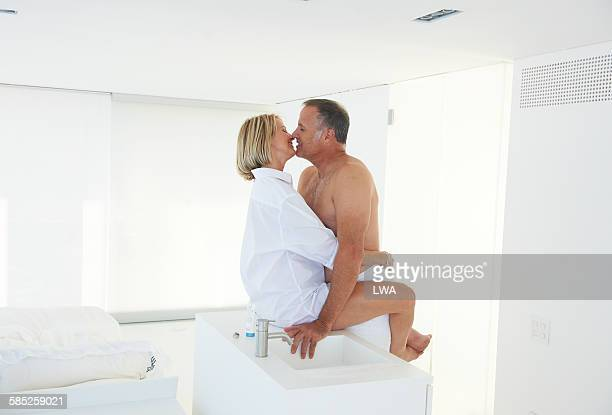 mature romantic couple in white room - couple and kiss and bathroom stock photos and pictures