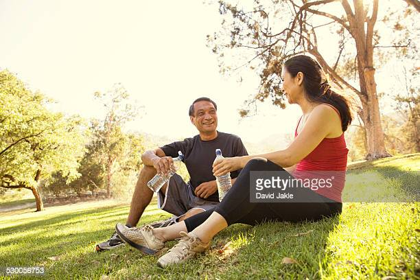 Mature running couple taking a break and drinking water in park