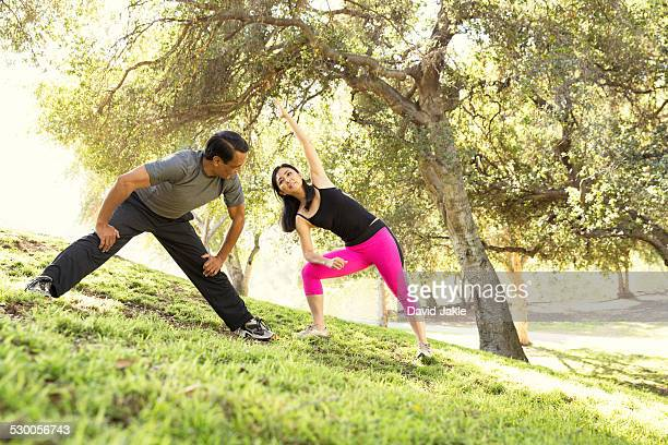 Mature running couple warming up together in park