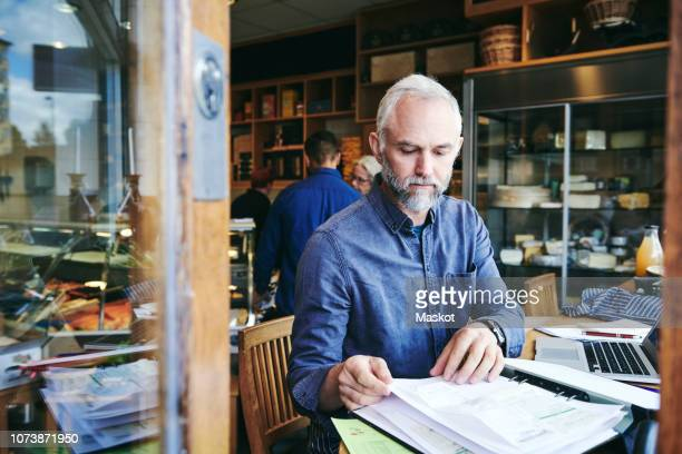 Mature sales clerk reading documents while sitting at table in deli