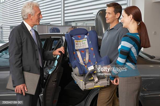 Mature salesman talking to couple with baby seat in car showroom