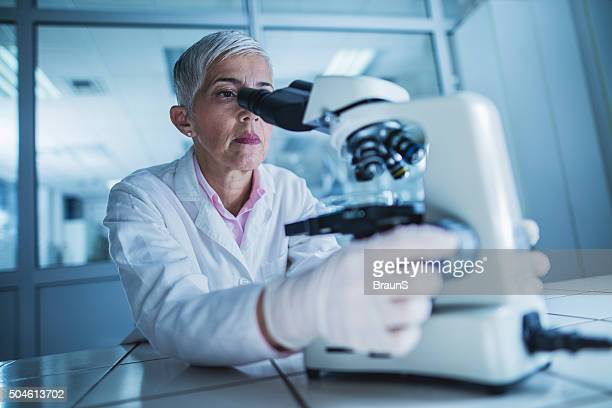 Mature scientist looking through a microscope in a laboratory.