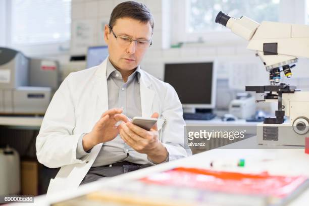 Mature scientist using mobile phone at laboratory