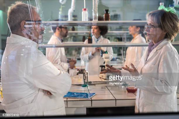 Mature scientists discussing about the research while working in laboratory.
