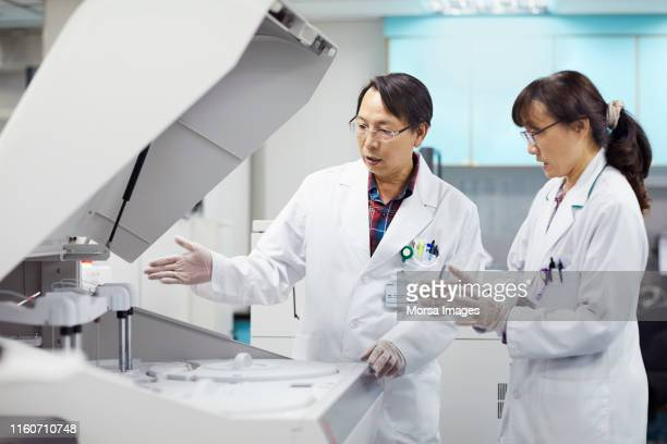 mature scientists discussing over centrifuge - centrifugador imagens e fotografias de stock