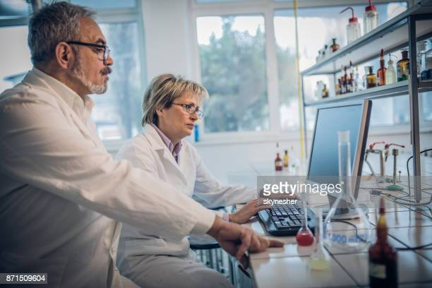 Mature scientists doing a research on desktop PC in a laboratory.