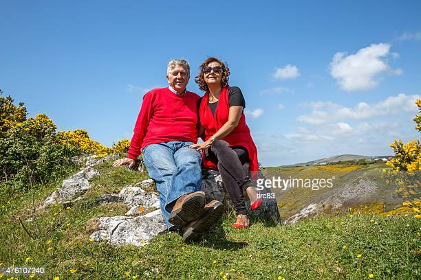 mature senior couple relaxing on coastal headland - gower peninsula stock photos and pictures