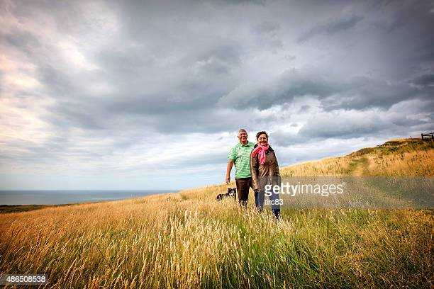 Mature senior couple walking on coastal headland with sheepdog