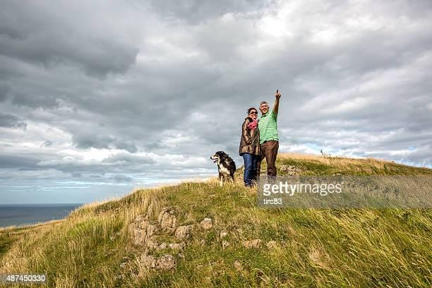 mature senior couple walking on coastal headland with sheepdog - gower peninsula stock photos and pictures