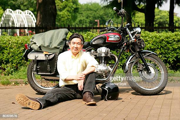Mature sitting next to motorcycle