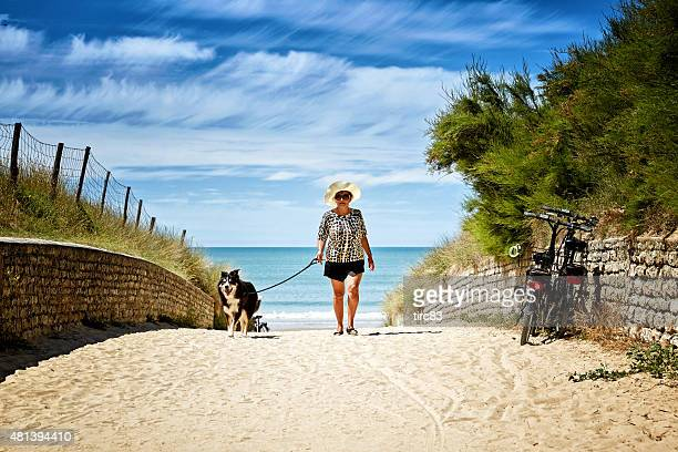 Mature smiling hispanic woman with dog walking on beach path