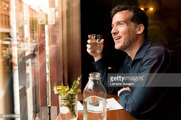 mature smiling man at restaurant looking out brooklyn window nyc - williamsburg new york city stock pictures, royalty-free photos & images
