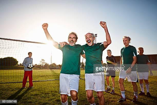 mature soccer players cheering - mannschaftssport stock-fotos und bilder