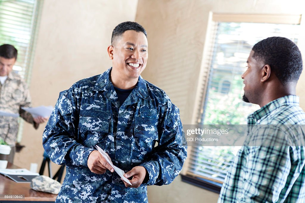 Mature soldier talking to young man at military recruitment event : Stock Photo