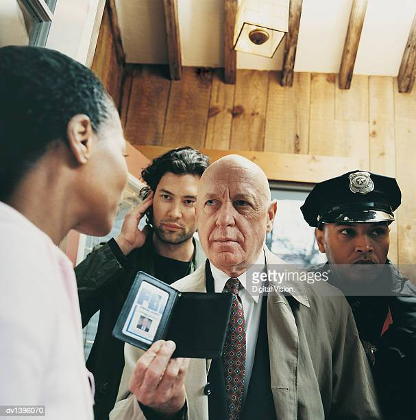mature special agent with colleagues in a house showing his id card to a woman - fbi id stock pictures, royalty-free photos & images