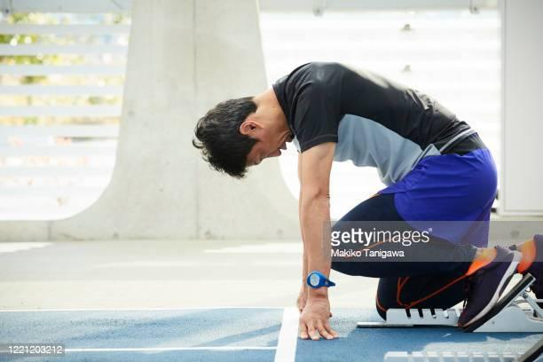mature sportsman at starting position - 再開 ストックフォトと画像