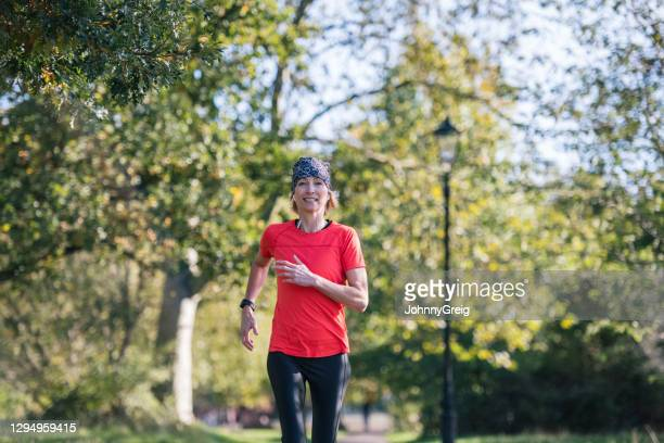 mature sportswoman enjoying afternoon run in public park - clapham common stock pictures, royalty-free photos & images