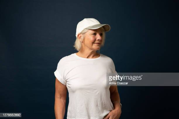 mature sporty woman looking at distance wearing baseball cap - t shirt stock pictures, royalty-free photos & images