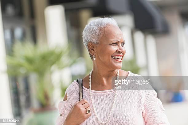 Mature, stylish African American woman walking on sidewalk