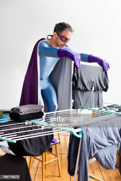 mature superhero drying laundry on rack against white wall - routine stock-fotos und bilder