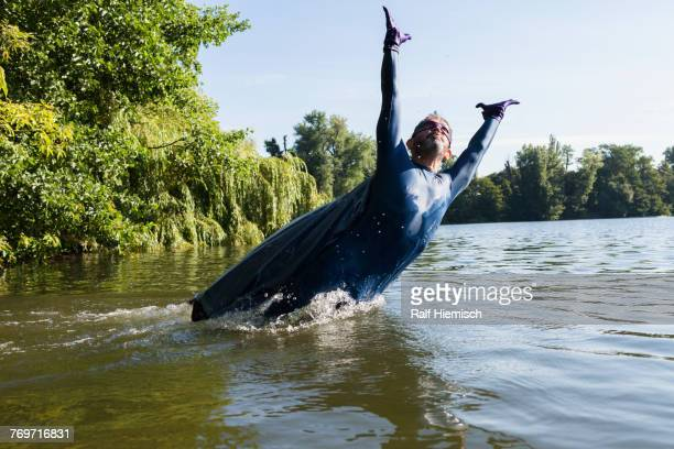 mature superhero jumping with arms raised in river against sky - flowing cape stock pictures, royalty-free photos & images