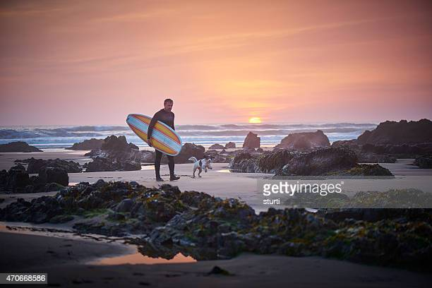 mature surfer leaving the surf at sunset greeted by dog - cornwall england stock pictures, royalty-free photos & images