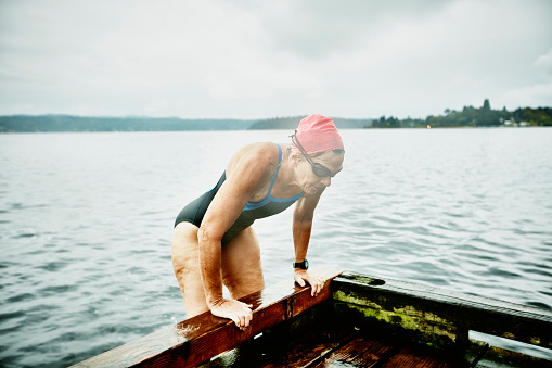 Mature swimmer climbing onto dock after swim - gettyimageskorea