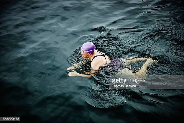 mature swimmer on early morning swim in lake - swimming goggles stock pictures, royalty-free photos & images