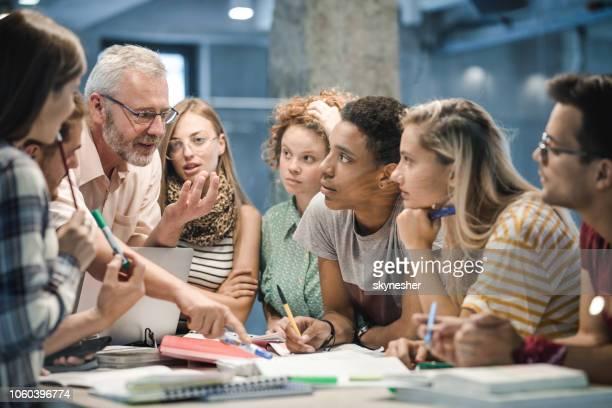 rijpe leraar lesgeven groep van studenten op de campus. - professor stockfoto's en -beelden