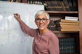 Mature teacher writing on whiteboard