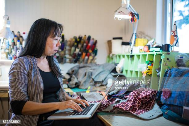 A mature textile entrepreneur working on a laptop computer in her studio