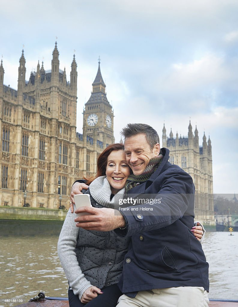 Mature tourist couple photographing selves and Houses of Parliament, London, UK : Stock Photo