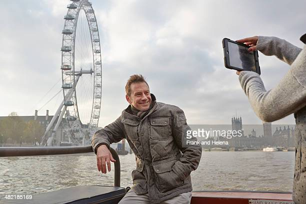 Mature tourist couple photographing selves and London Eye, London, UK