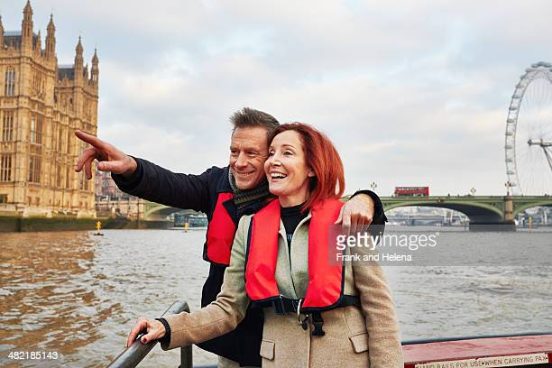 Mature tourist couple sightseeing on Thames boat, London, UK