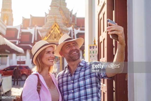 Mature Tourist Couple Taking Selfies At Bangkok Palace