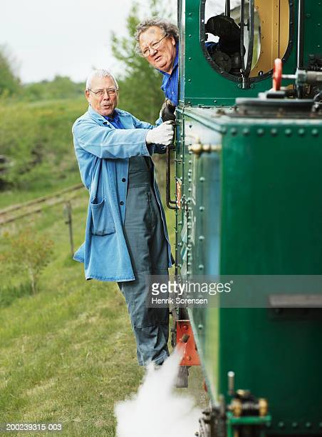 mature train driver leaning out of engine window, mechanic on steps - green coat stock pictures, royalty-free photos & images