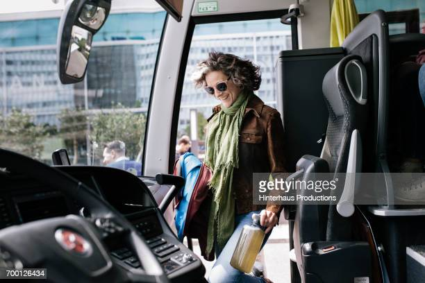 mature traveler boarding a bus - coach bus stock photos and pictures