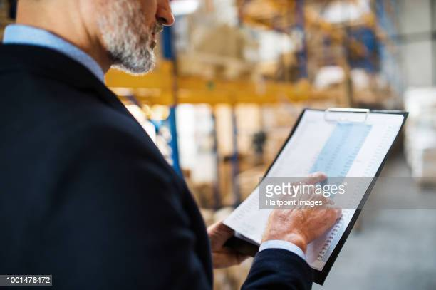 mature warehouse man manager with clipboard, checking something. - loader reading stock pictures, royalty-free photos & images