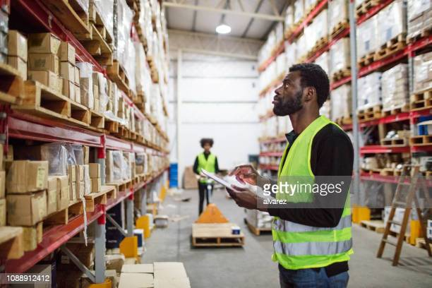 mature warehouse worker checking inventory - reflective clothing stock pictures, royalty-free photos & images