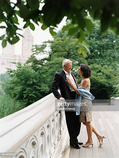 Mature, Well-Dressed Couple Stand Face to Face on a Bridge in Central Park, Talking and Smiling