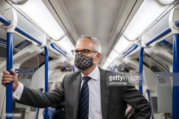 mature white collar worker commuting in protective face mask - pole stock pictures, royalty-free photos & images