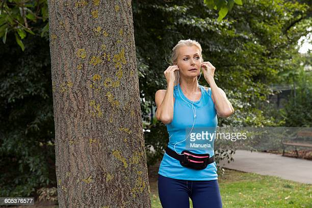 Mature woman adjusting earphones whilst training in park