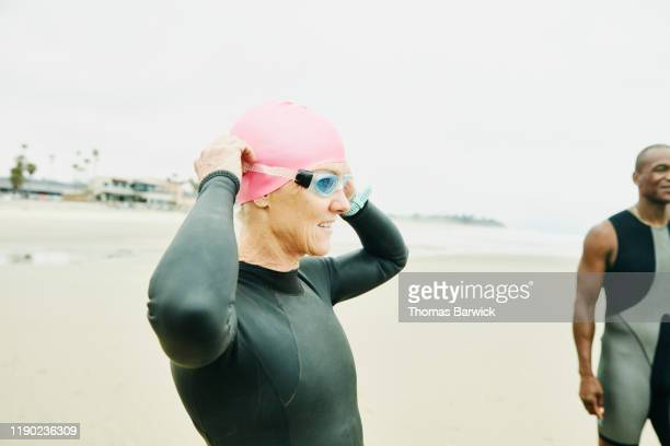 mature woman adjusting goggles before early morning open water swim with friends - active lifestyle stock pictures, royalty-free photos & images