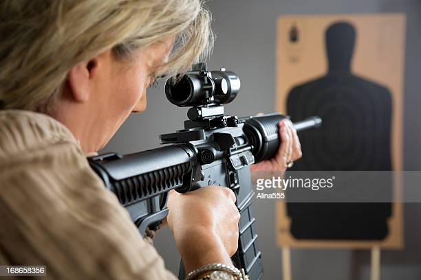 mature woman aming rifle at a target - gun barrel stock pictures, royalty-free photos & images