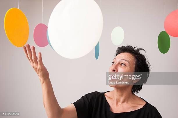 Mature woman among colorful paper circles