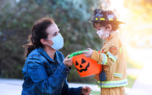 Mature woman and a child boy wearing protective face masks before going to ask trick or treat halloween 1275660773