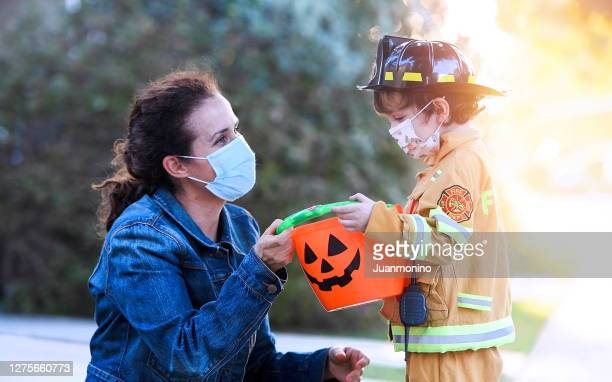 mature woman and a child boy wearing protective face masks before going to ask trick or treat halloween - halloween stock pictures, royalty-free photos & images