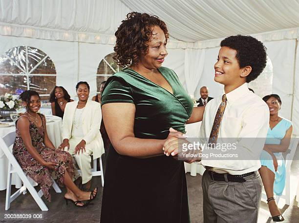 Mature woman and boy (10-12) dancing, extended family watching